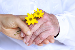 elder and caregiver hand in hand